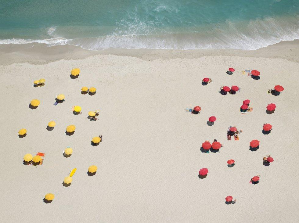 Vista aérea de unas sombrillas en la playa formando un patrón.