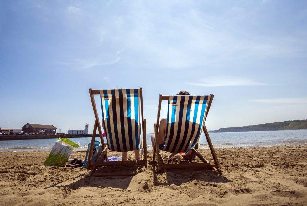 Una pareja disfruta del calor en una playa de Scarborough, Inglaterra.