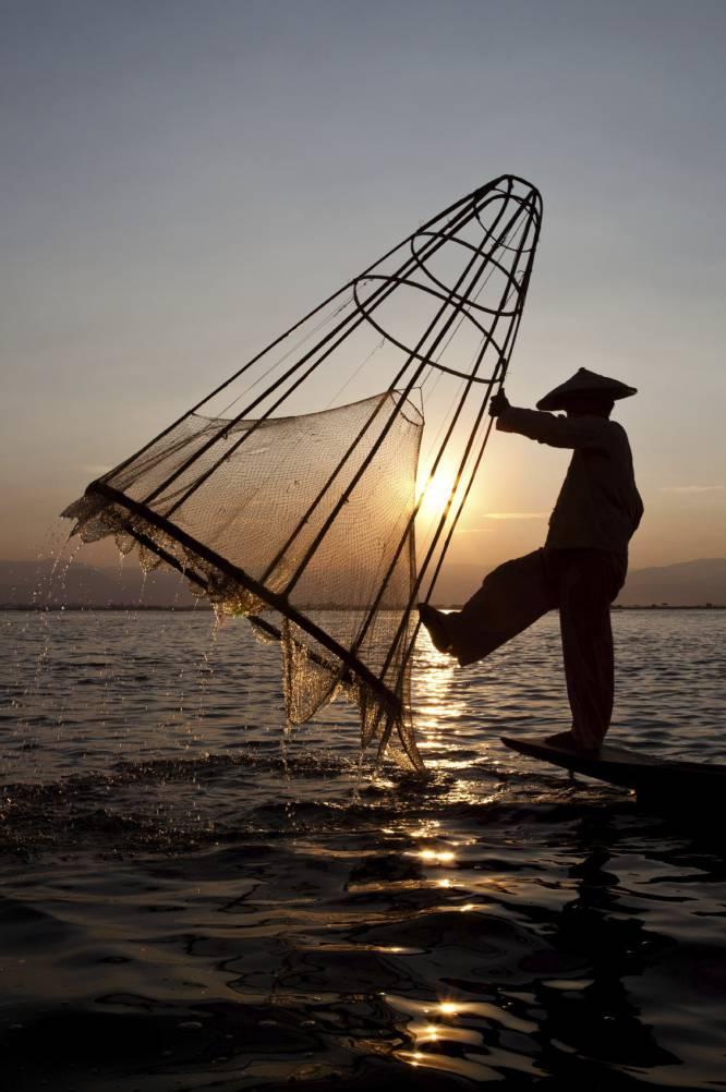 Un hombre pescando a la luz del atardecer.