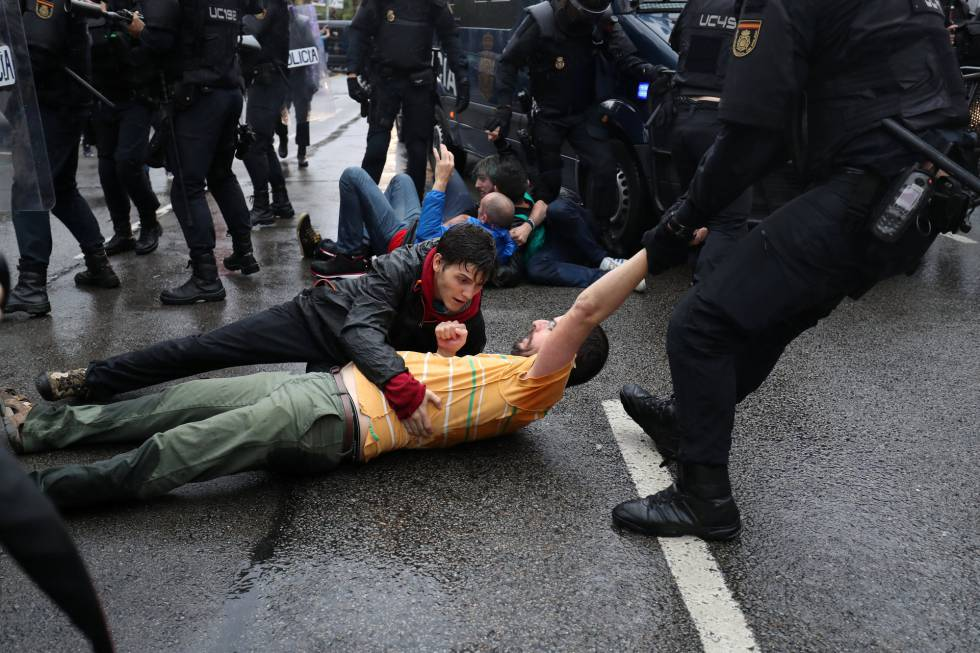 Riot police remove demonstrators outside a polling station for the banned independence referendum in Barcelona.