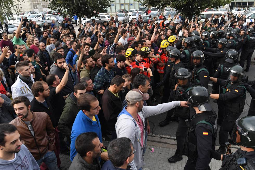 Crowds raise their arms up to the police on October 1, 2017 in Sant Julia de Ramis, Spain.