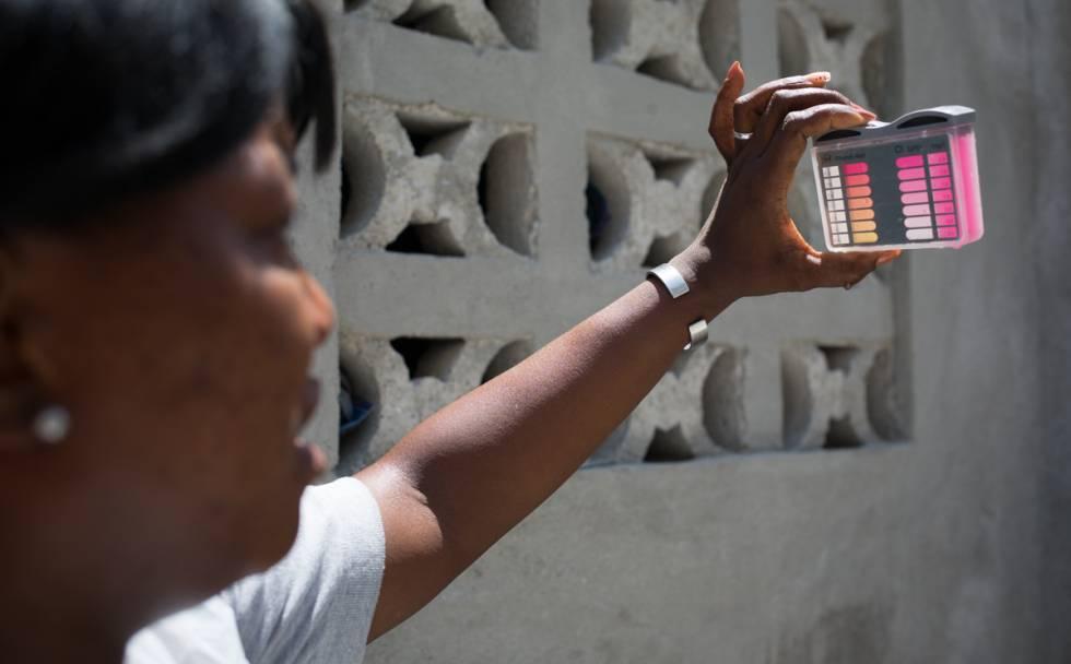 Una técnico controla el agua en una casa donde se han dado casos de cólera, cerca de Puerto Príncipe (Haití).
