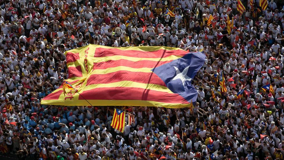 Una inmensa bandera estelada pasa entre las manos de los participantes en una celebración de la Diada.