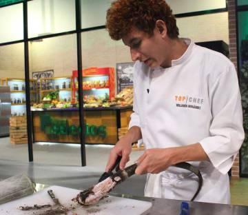 Un cocinero pela la cola de una iguana ya cocida el domingo en la televisión de El Salvador.