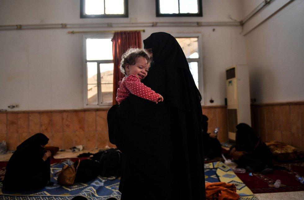Una niña en brazos de su madre ríe mientras esperan en la frontera oeste de Raqa, Siria el 8 de octubre.