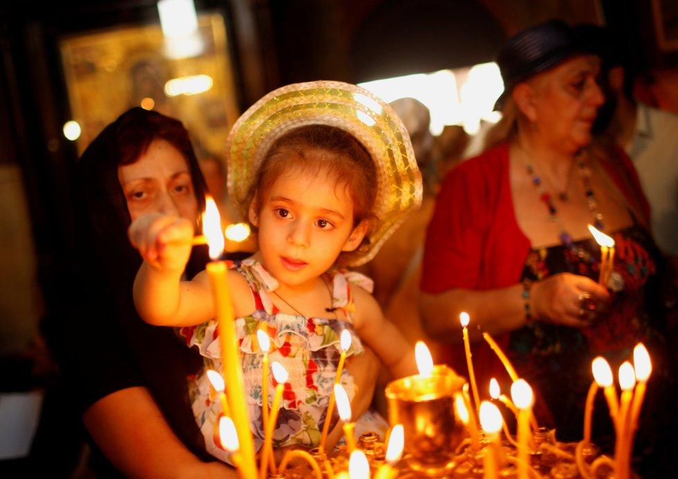 Una niña enciende una vela durante el servicio religioso por el día de la Virgen María en la catedral de Sioni en Tbilisi, Georgia, el 28 de agosto.