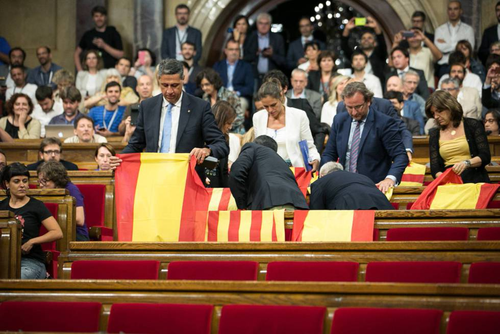 Deputies inside the Catalan parliament exhibiting Spanish and Catalan flags.