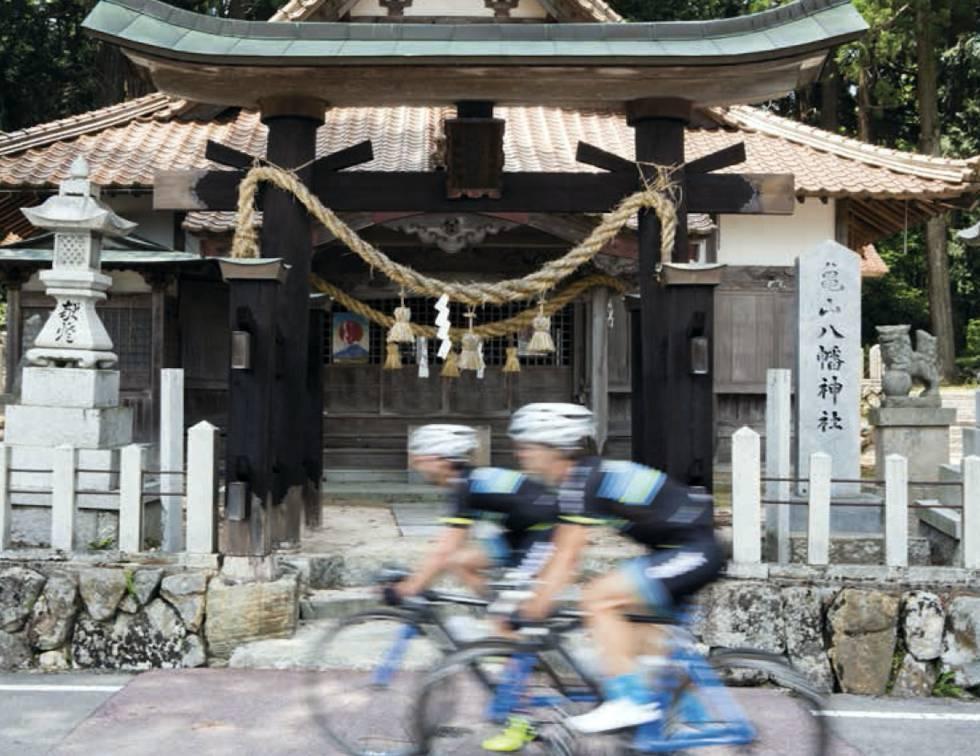 Una pareja de ciclistas pasa frente a un templo en Japón