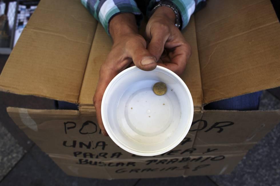 Un mendigo sujeta un vaso de plástico mientras pide dinero en Madrid.rn rn