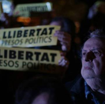 "A man protests the pre-trial detention of former Catalan ministers on Thursday; the banners behind read: ""Freedom for the political prisoners."""