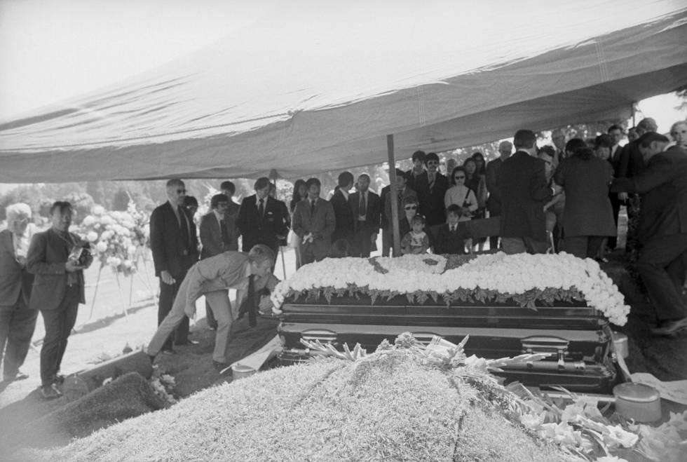 El actor Steve McQueen besa la tumba de Bruce Lee en el fumeral celebrado en Seattle en 1973. Al fondo, sentados, la viuda de Lee, Linda C. Emery, y sus hijos Brandon y Shannon.