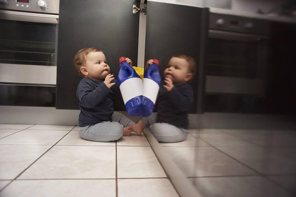 Un bebé se hace con un producto de limpieza en una cocina.