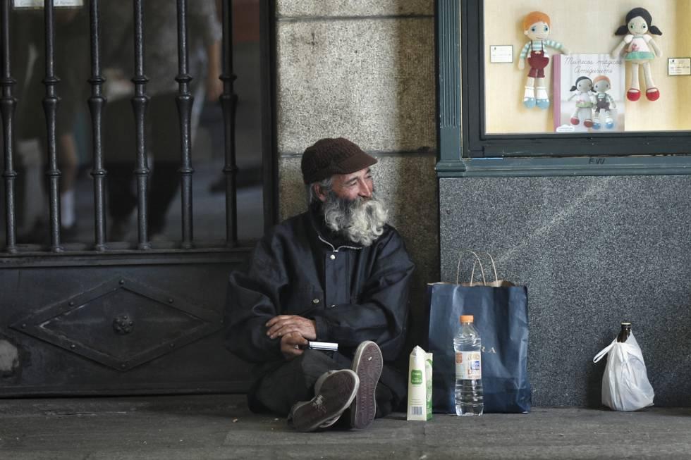 Un mendigo, un hombre mayor, pide limosna en los soportales de la plaza Mayor de Madrid.