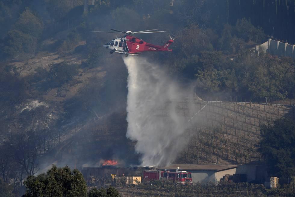 Un helicóptero de los bomberos apaga el fuego que afecta al viñedo propiedad de Rupert Murdoch en el barrio de Bel Air, en California.