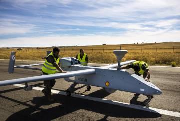 De arriba abajo, técnicos del INTA inspeccionan drones con sensores visibles e infrarrojos, destinados a misiones de reconocimiento y vigilancia; un piloto guía una aeronave robótica desde la cabina de mando en tierra, y operarios revisan un Searcher MKII J en León.