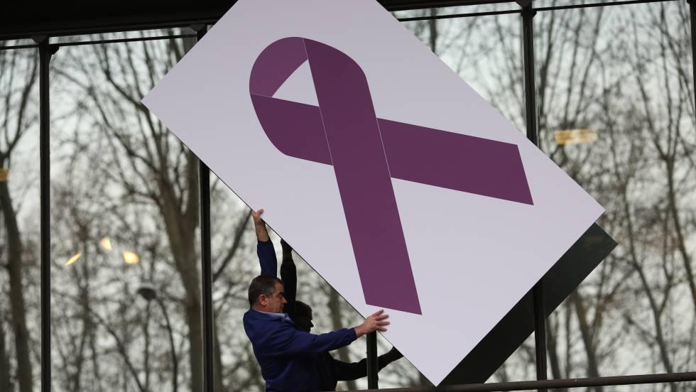 Minuto de silencio en el Ministerio de Sanidad. Un operario coloca un panel con una lazo gigante rosa en contra de la violencia de género.