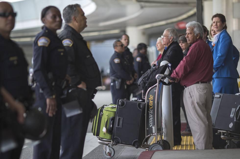 Agentes de policía y viajeros en la salida de un aeropuerto.rn