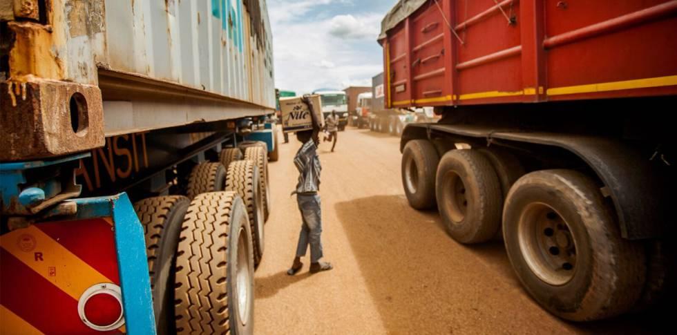 Un niño se busca la vida vendiendo agua mineral a los camioneros que esperan en la cola.