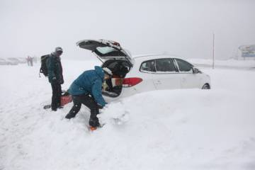 Two people dig their car out from the snow in Navacerrada, Madrid.