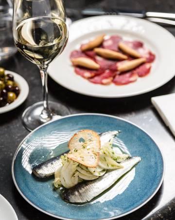 Plato de presa ibérica y sardinas con ensalada del restaurante Sabor.