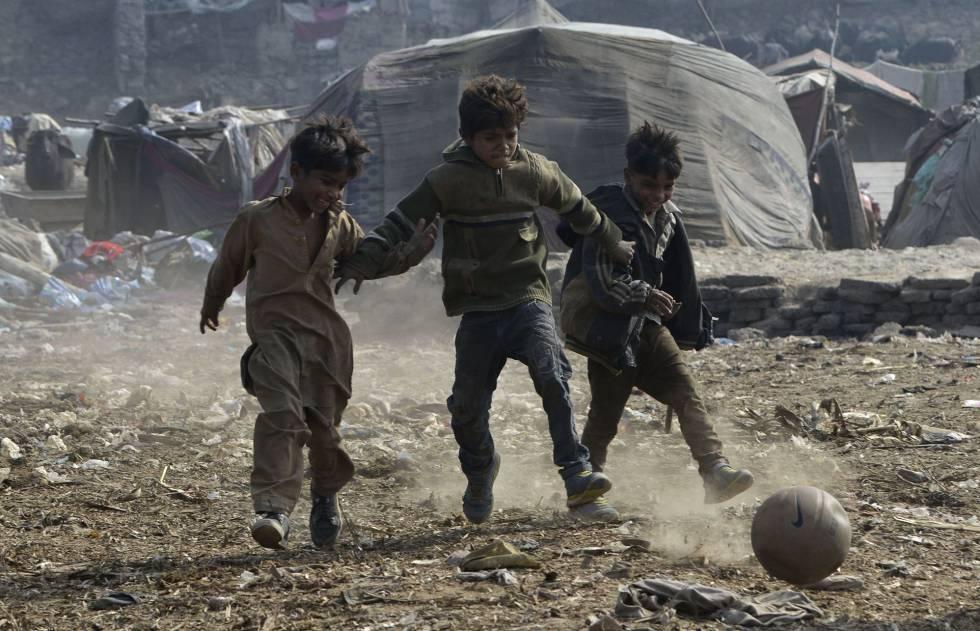 Niños paquistaníes juegan a fútbol en un barrio chabolista de Lahore.