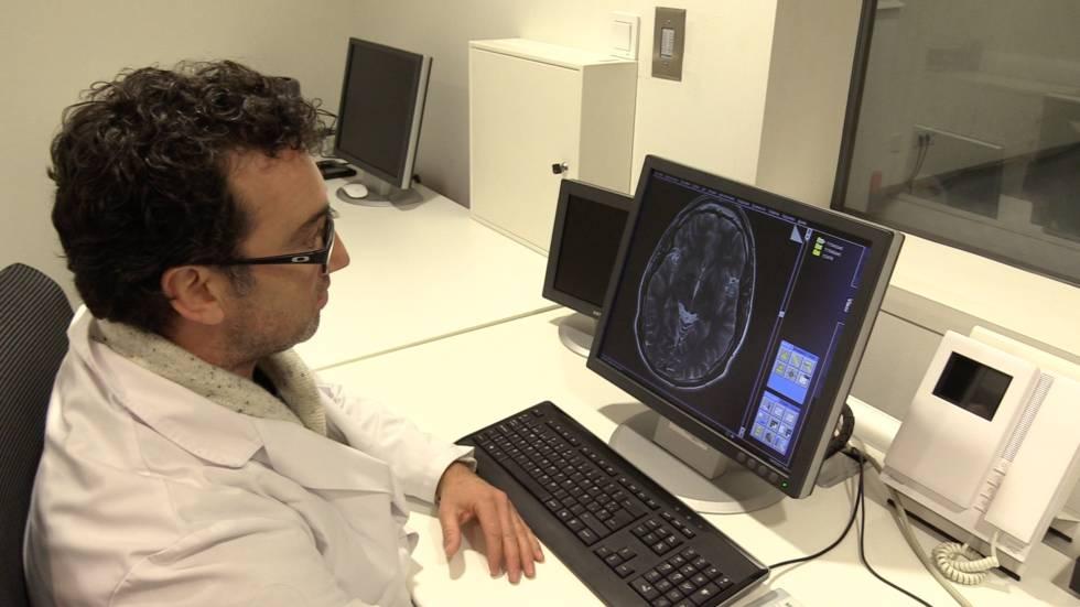 Un científico observa un cerebro en el ordenador.