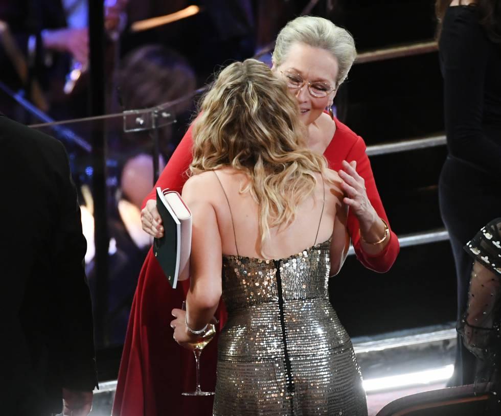 Por fin llega a uno de sus objetivos: saludar a Meryl Streep, que no lleva una copa de vino y sí un bolso y un cuaderno.