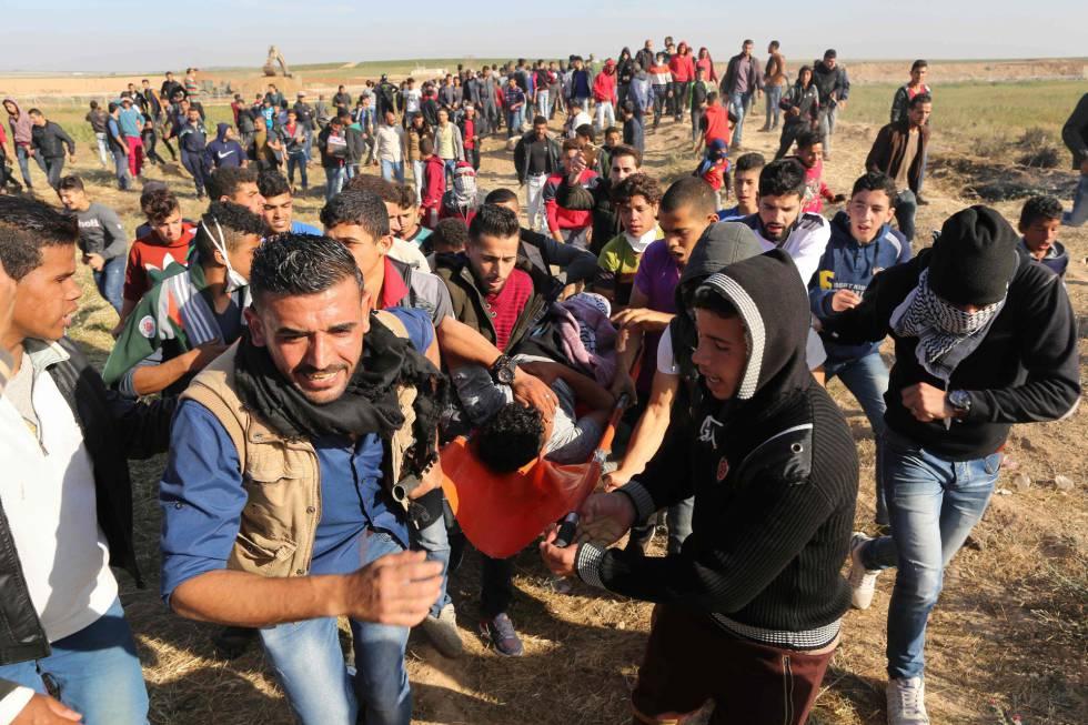 Varios manifestantes llevan a un herido de bala durante la manifestación junto al límite de Gaza.
