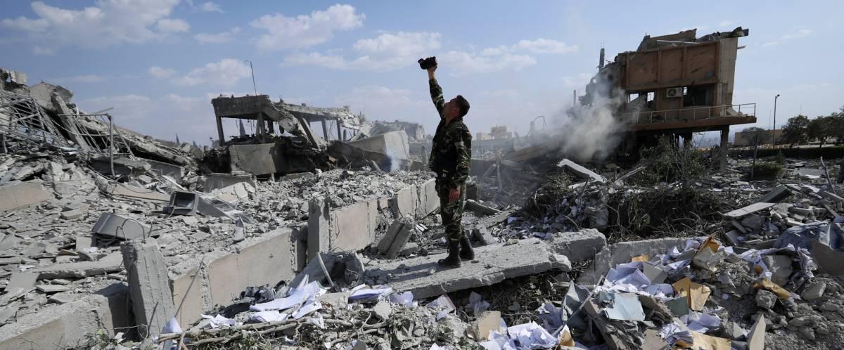 Un soldado sirio sobre las ruinas de unos de los complejos atacados por EE UU y sus aliados.