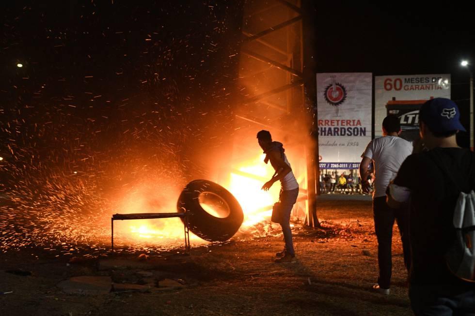 Un profesor lanza un neumático ardiendo contra uno de los árboles artificiales colocados por el Gobierno sandinista en Managua.