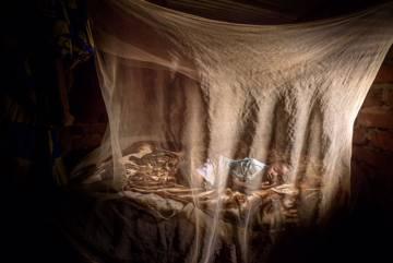 Un niño duerme debajo de una mosquitera en Burundi.