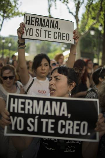 Protesters in Seville hold up signs reading