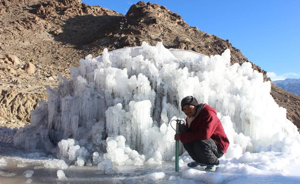 Trabalhador posa junto a uma estupa de gelo em processo de construção