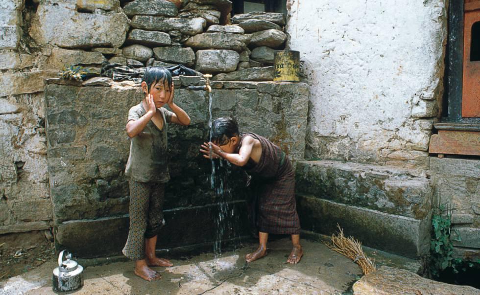 Dos niños se bañan con el agua de una fuente para beber en Bután.