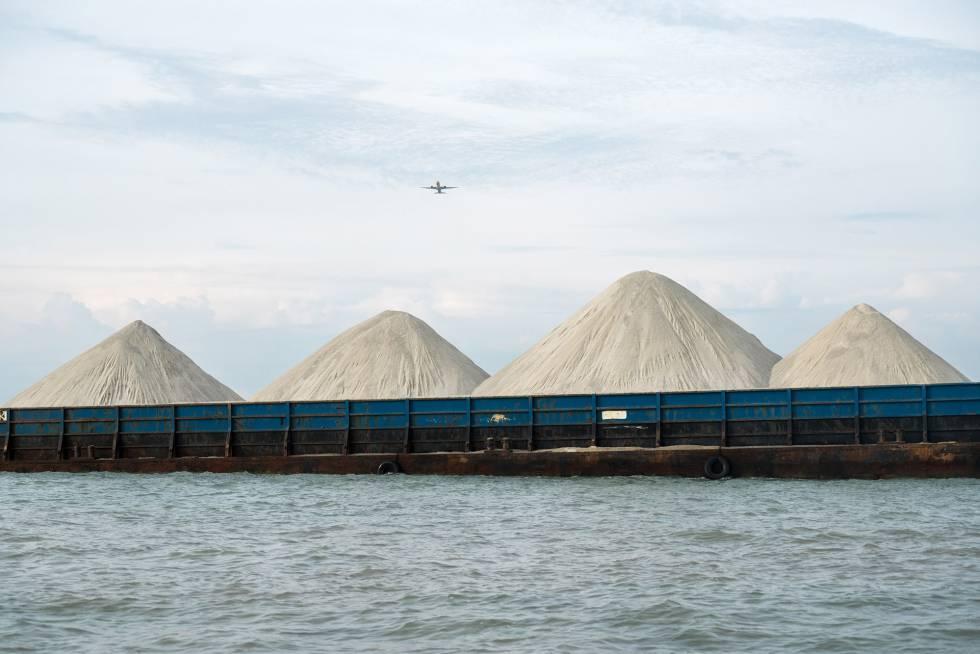 Montañas de material para la construcción, probablemente con arena mezclada con granito, entran en un puerto occidental de Singapur en barco.