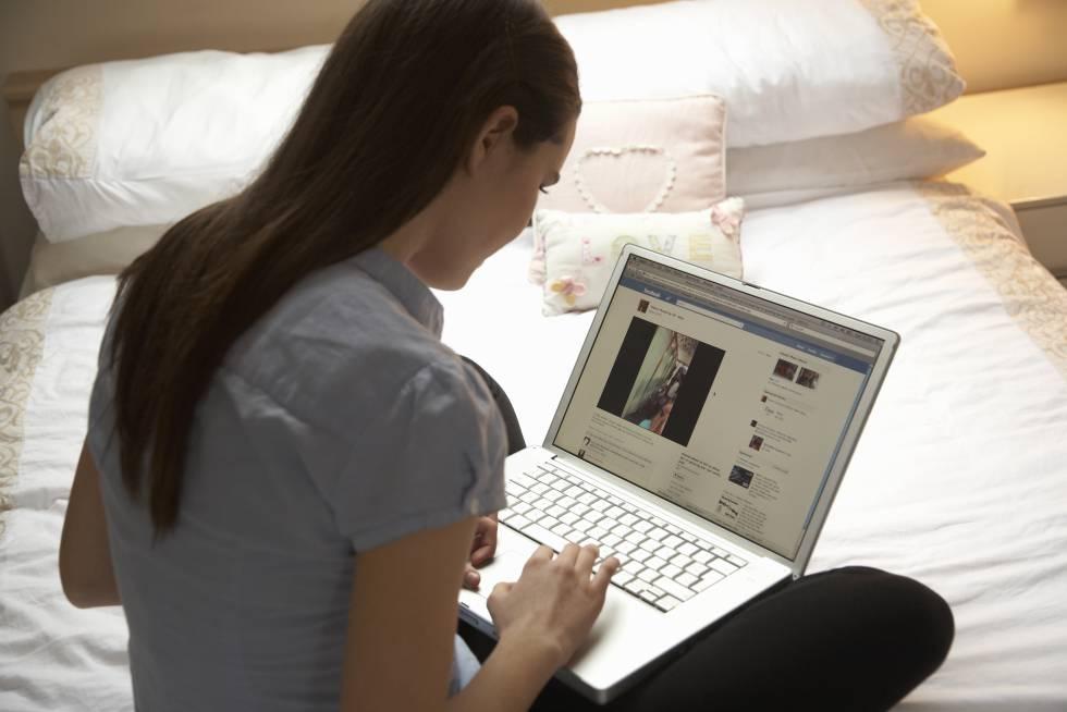 Un joven mira Facebook en su ordenador.