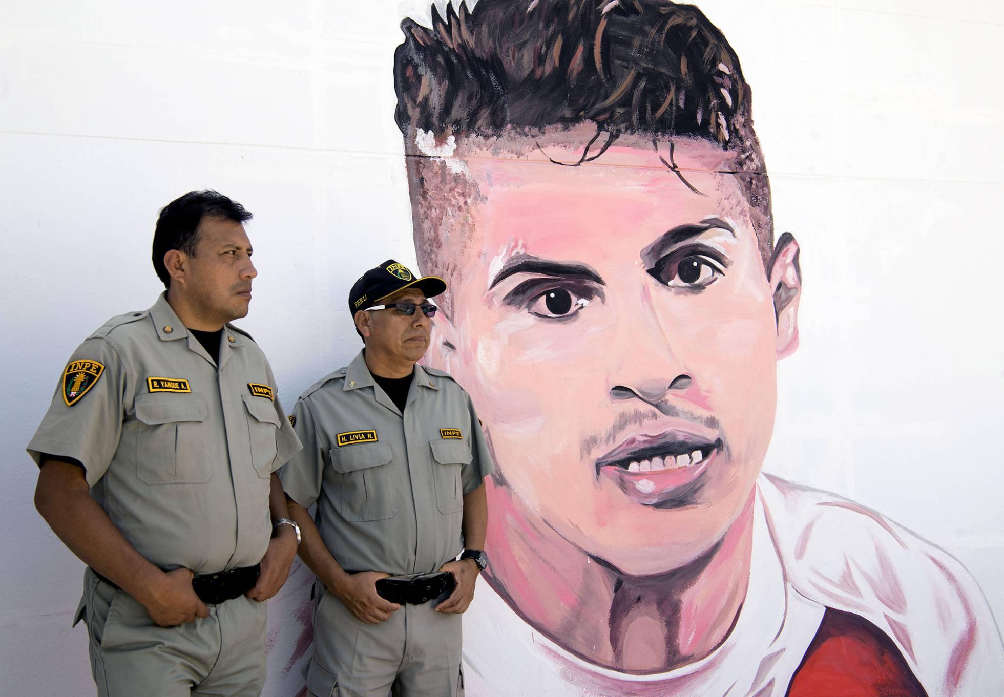 Dos policías delante de un grafiti con el rostro del futbolista Paolo Guerrero, una de las estrellas de la selección de Perú. CRIS BOURONCLE