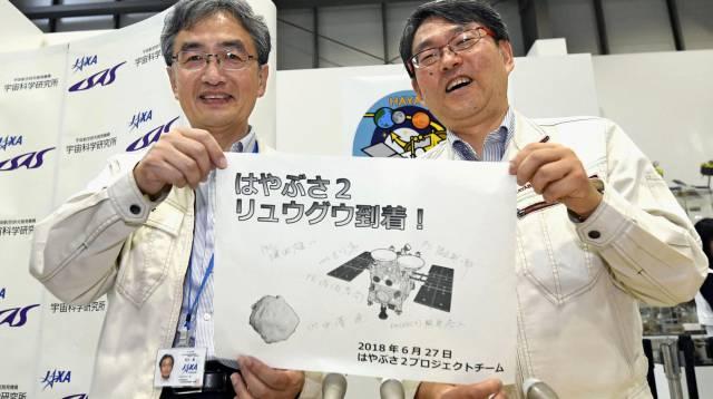 Takashi Kubota y Makoto Yoshikawa, de la Agencia Espacial Japonesa (JAXA), con un dibujo de la sonda Hayabusa 2.