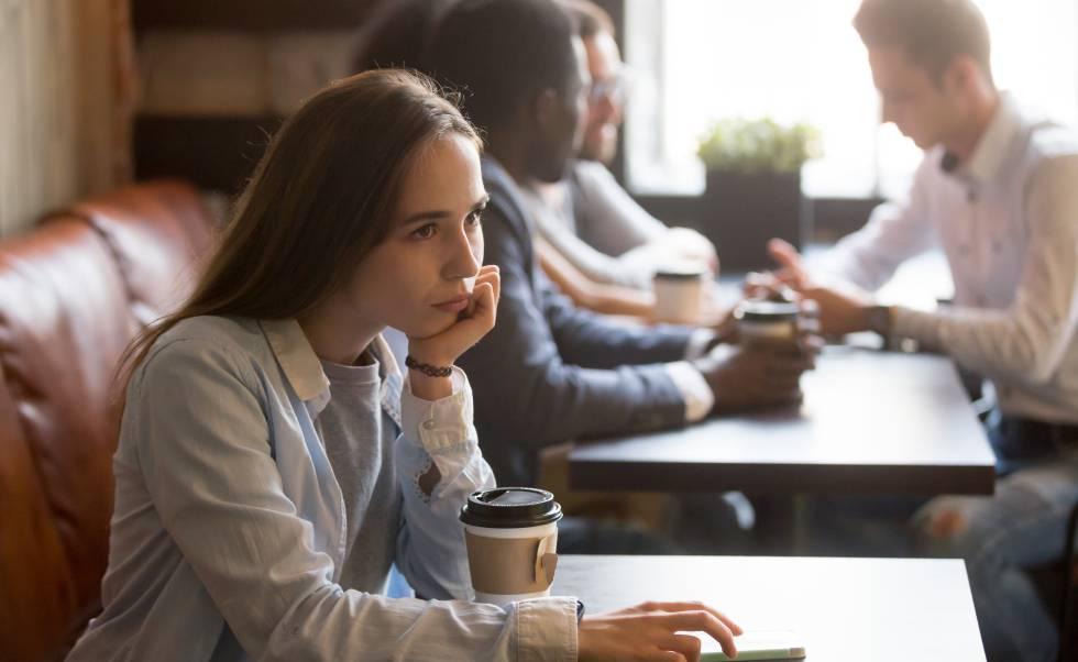Una joven, sentada sola en un café. Detrás, un grupo de personas comparte una mesa.
