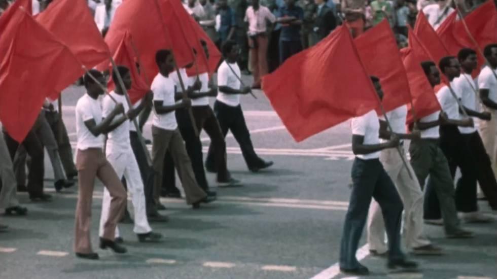 Desfile de civiles en África con banderas comunistas.