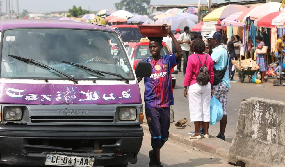 Un chico togolés vende agua potable fría en una parada de taxis de Libreville el 25 de junio de 2018.