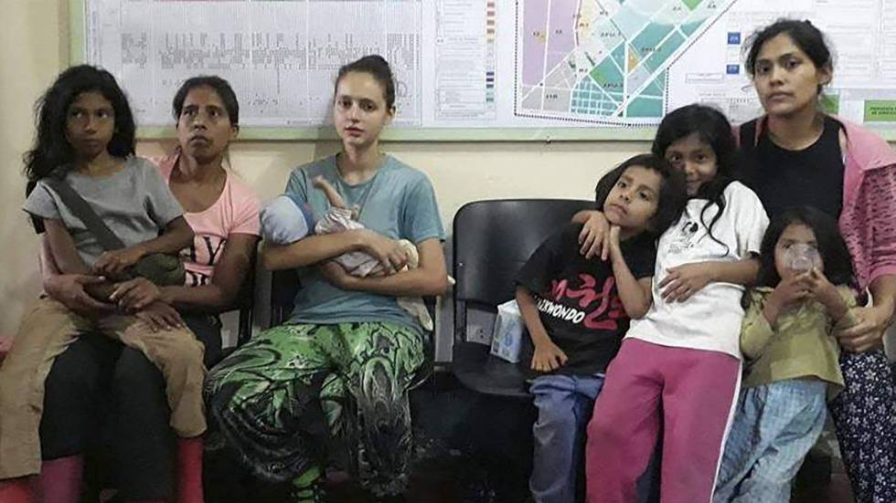Patricia Aguilar, third from left, holding her baby after being rescued.