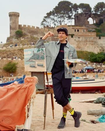 Andrés se ha puesto abrigo y botas Prada, camiseta y pantalón Shoop y calcetines Alyx. Al fondo, el Castillo de Tossa de Mar.