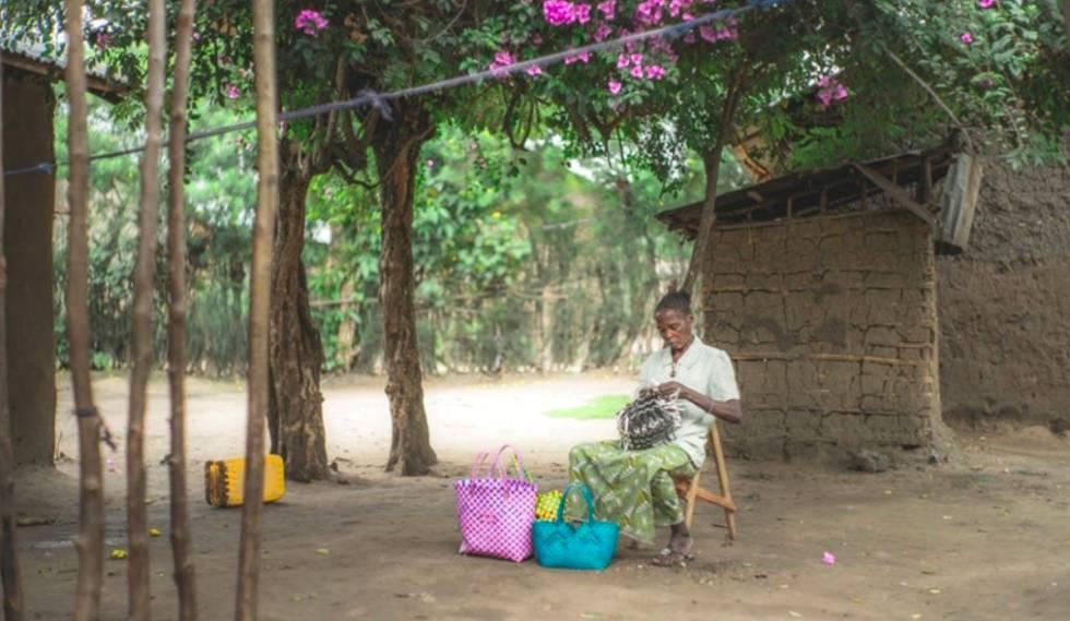 Speciose Mapendo teje cestos frente a su casa de Kiwanya (R.D. Congo).