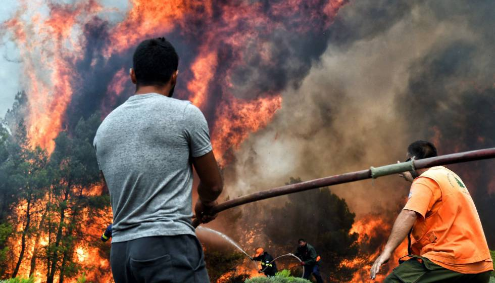 Varios bomberos y voluntarios luchan contra las llamas en un incendio en Verori, cerca de Loutraki (Grecia).