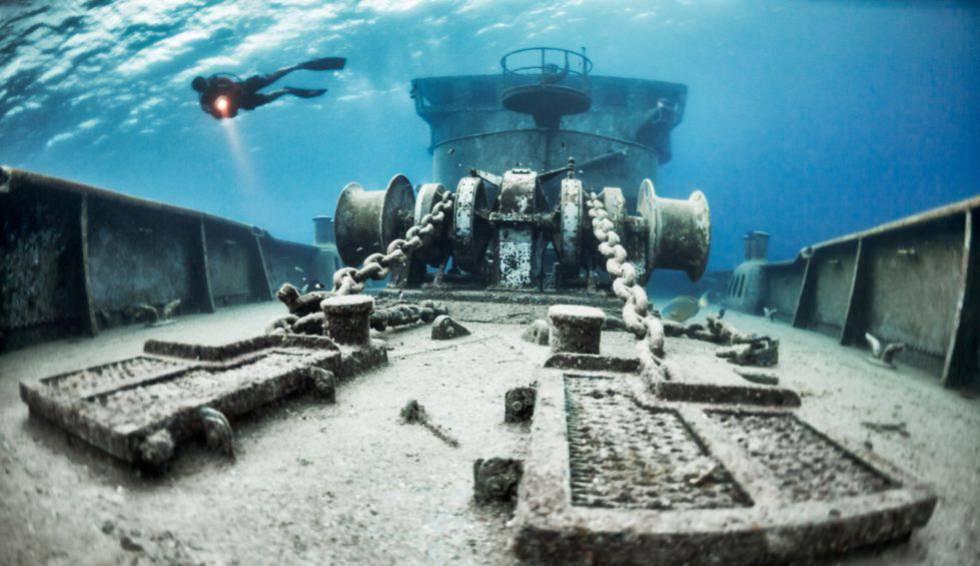 Un buzo, sobre un barco hundido en aguas de las Islas Caimán.