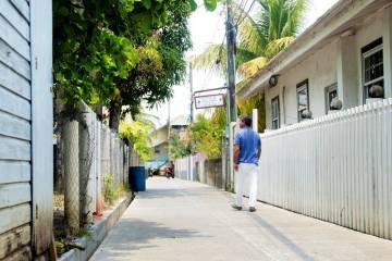 Troy Bodden, alcalde de Utila, camina por la calle Holland, la primera de Honduras pavimentada con asfalto hecho con plástico reciclado.
