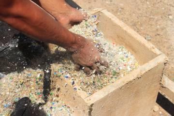 Un trabajador toma plástico reciclado para preparar el asfalto. Calle Lozano es la segunda calle de Utila hecha con plástico.