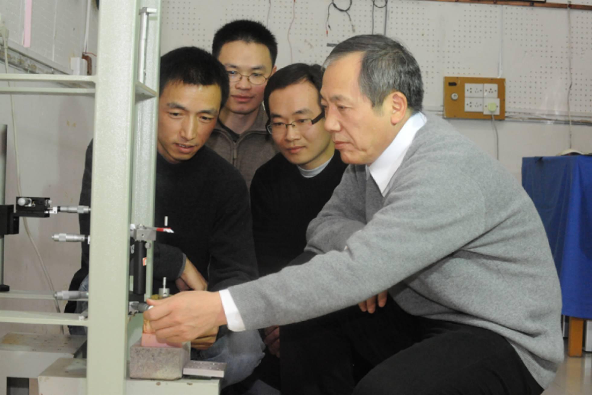 O físico Luo Jun (direita) e sua equipe, junto a um de seus aparelhos.