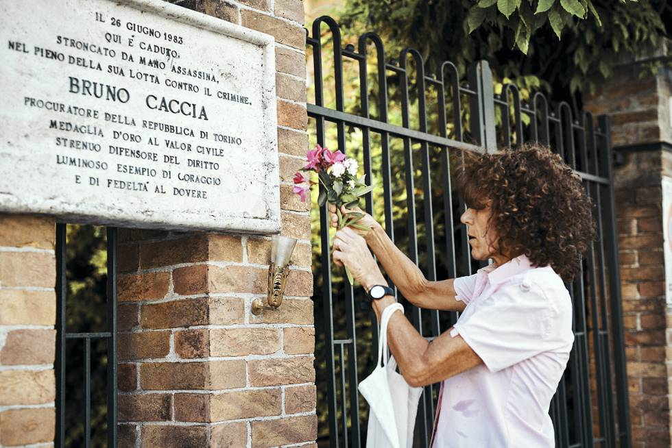 A filha do magistrado de Turim, Bruno Caccia, assassinado pela 'Ndrangheta em 1983, coloca flores na placa que lembra dele.